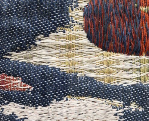 close up shot of weaving, blues reds greens woven in different patterns meeting